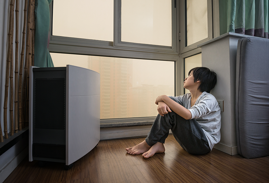 Boy sitting next to air purifier